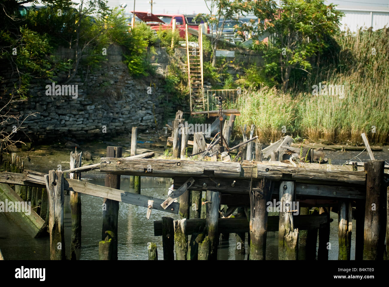 Abandoned pier along Newtown Creek an industrial waterway separating the boroughs of Brooklyn and Queens in New - Stock Image