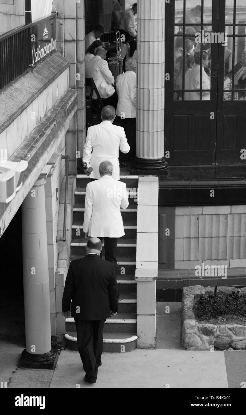 Musiciand climbing steps to a seafront bandstand for a concert in Eastbourne - Stock Image