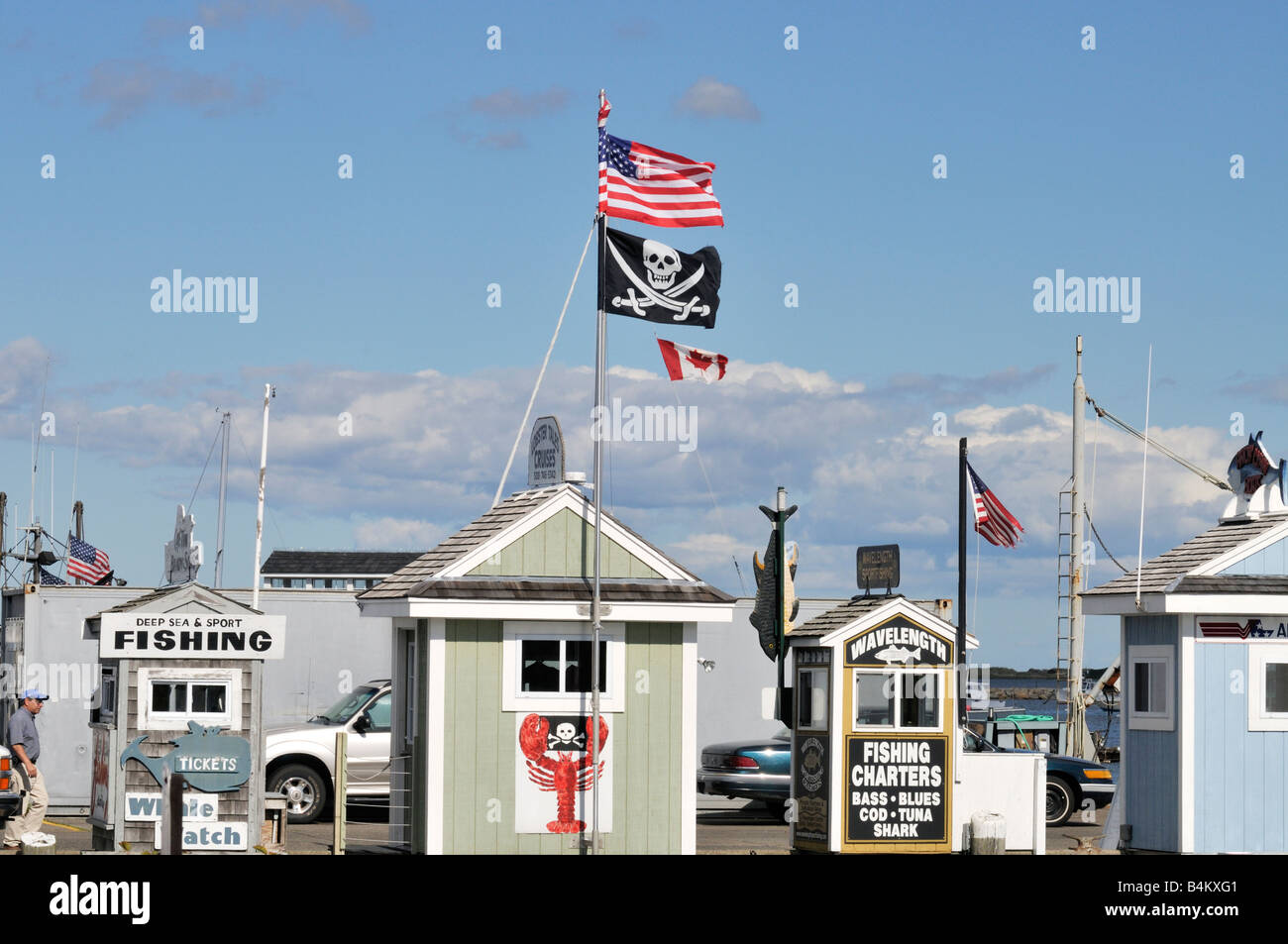 Row of charter fishing ticket booths on pier with American, Canadian and Pirate flags on sunny day in Plymouth Harbor, - Stock Image