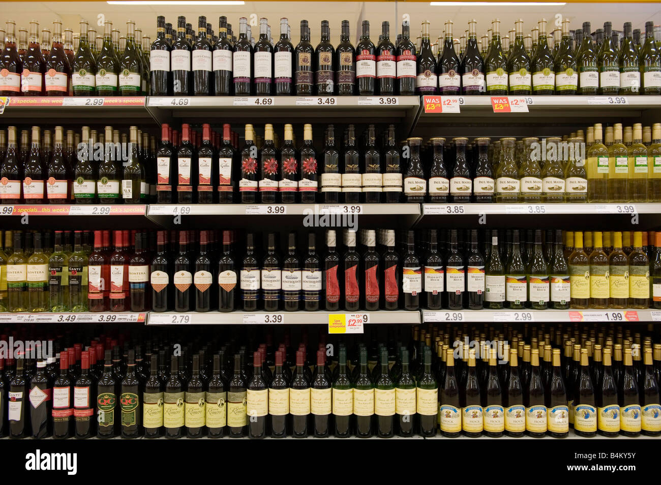 Bottles of cheap red wine on shelves in a budget supermarket in the UK - Stock Image
