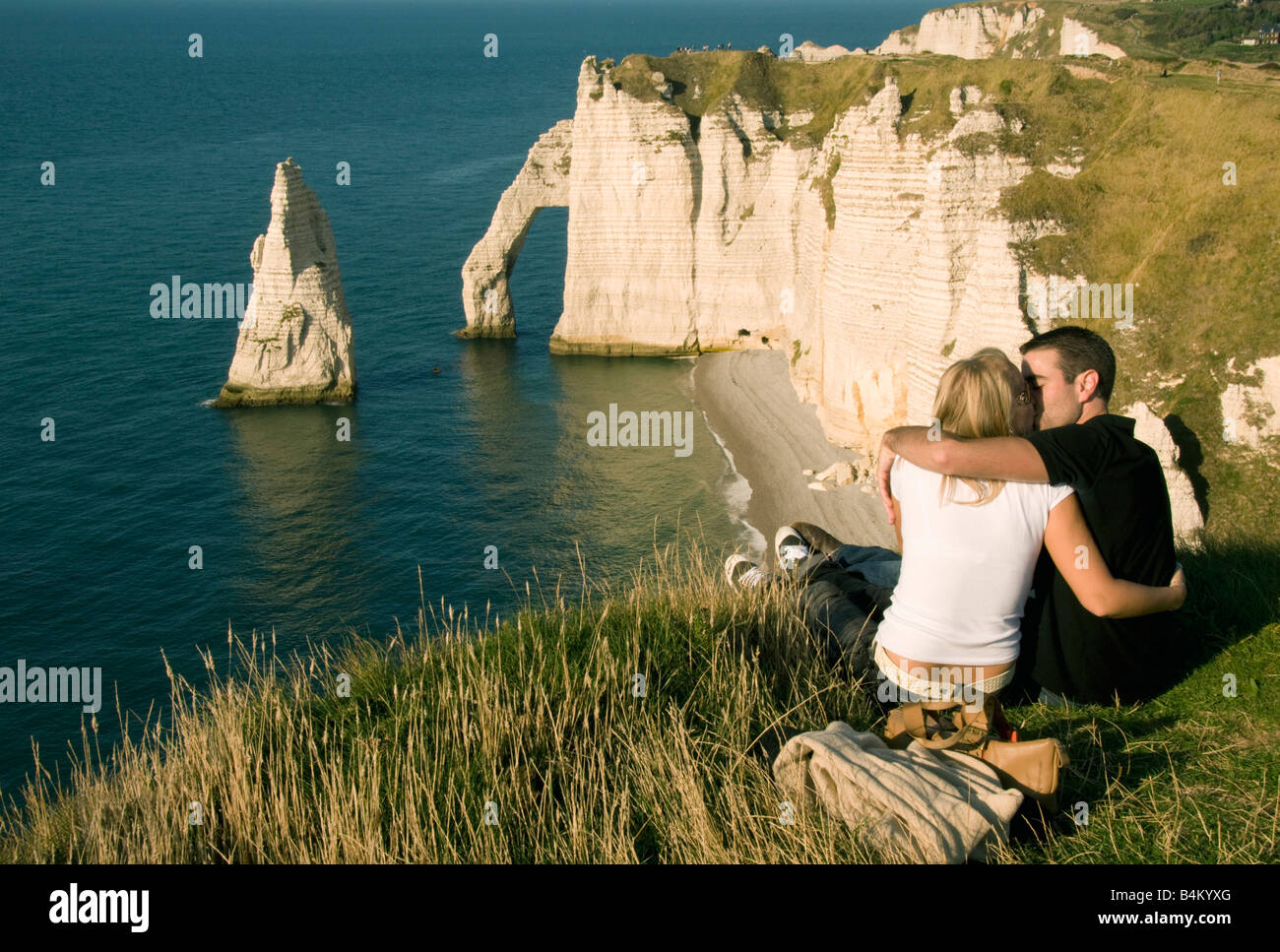 France, Normandy, Coast, Etretat, couple spend sunset above Porte d'Aval Arch and l'Aiguille (Needle) - Stock Image