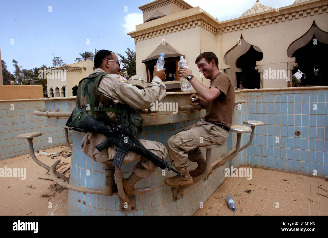 Iraq War 2003 US infantrymen try out the pool bar at Saddam s son Uday s entertaining palace discovered by elements - Stock Image