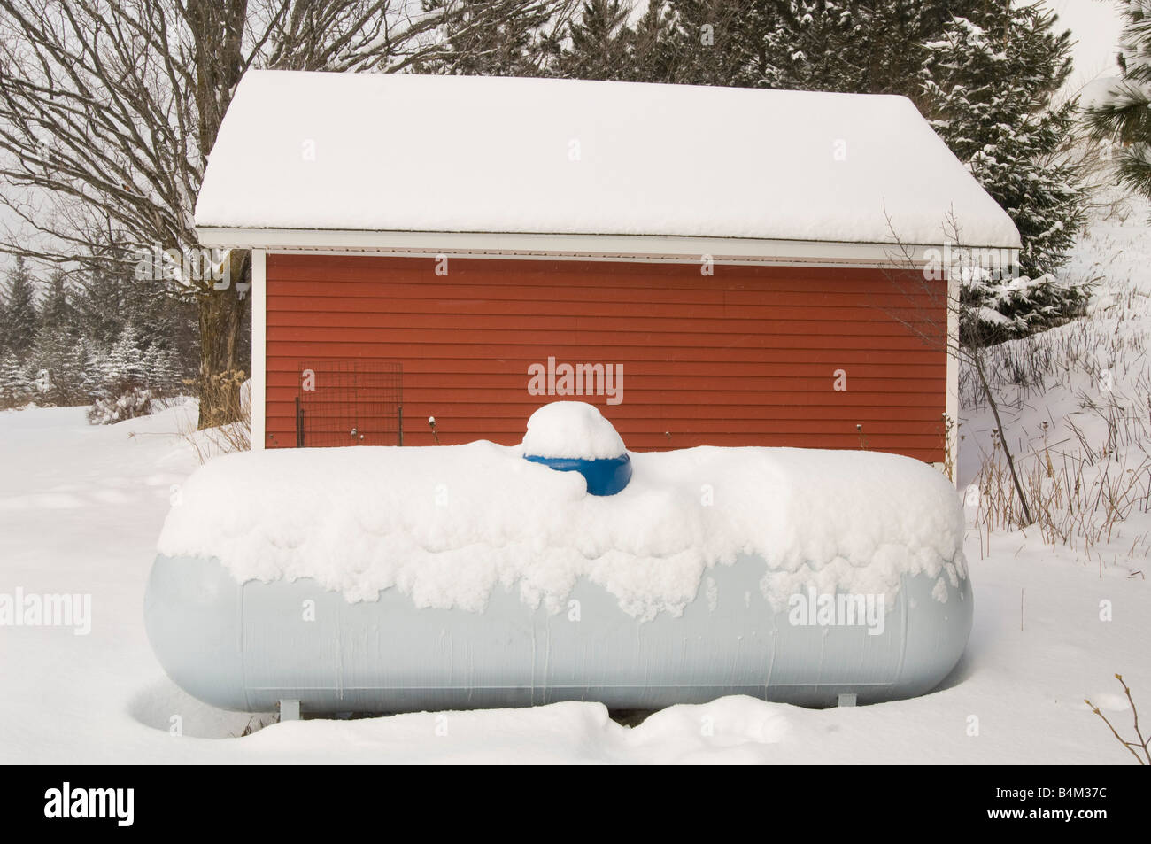 A snow covered propane LP tank and red farm building during winter - Stock Image