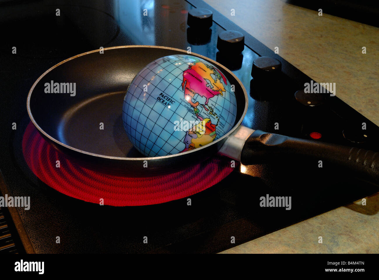 A globe is shown frying in a skillet on a hot stove burner representing the concept of Global Warming - Stock Image