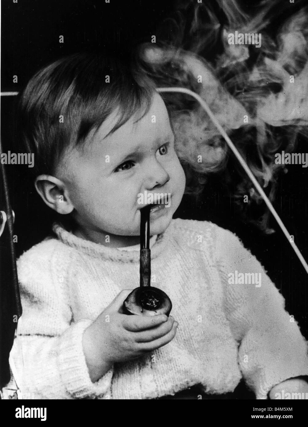 Lee Goult 17 months smokes his cherrywood pipe his father Allan Goult says he was smoking before his first birthday - Stock Image