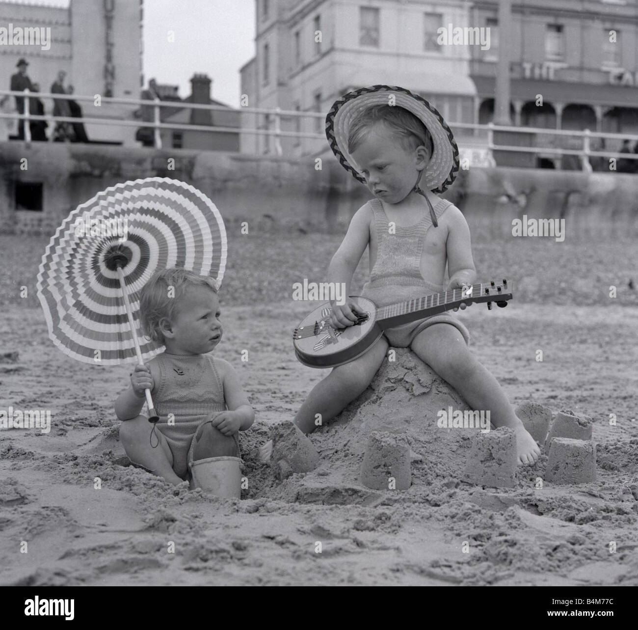 A small boy serenades his little sister on the beach whilst enjoying the May Bank Holiday sunshine May 1954 - Stock Image