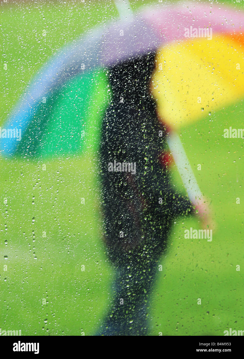 person stood with umbrella in the rain - Stock Image