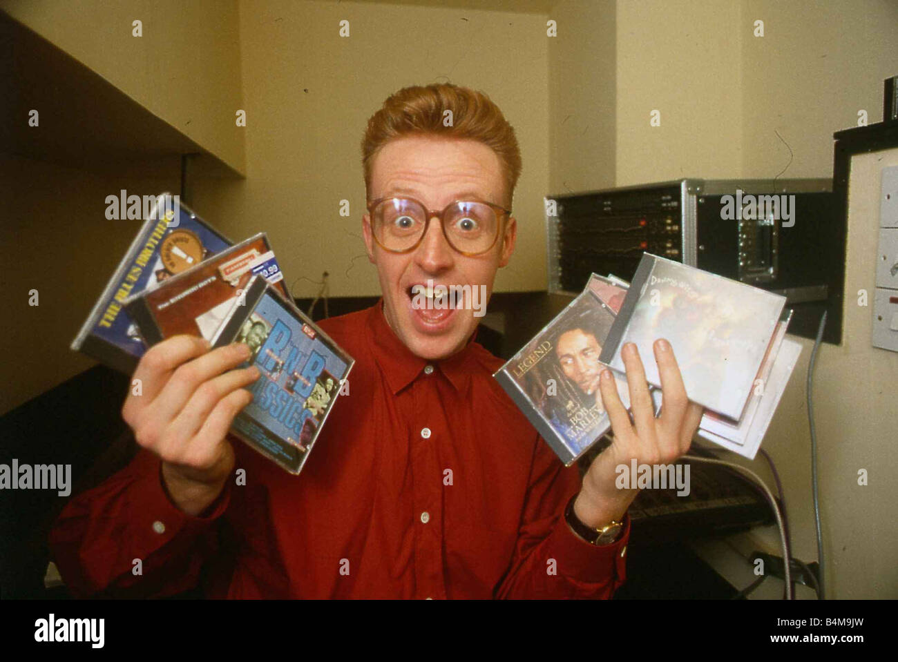 TV presenter Bryan Burnett holding various CD s - Stock Image