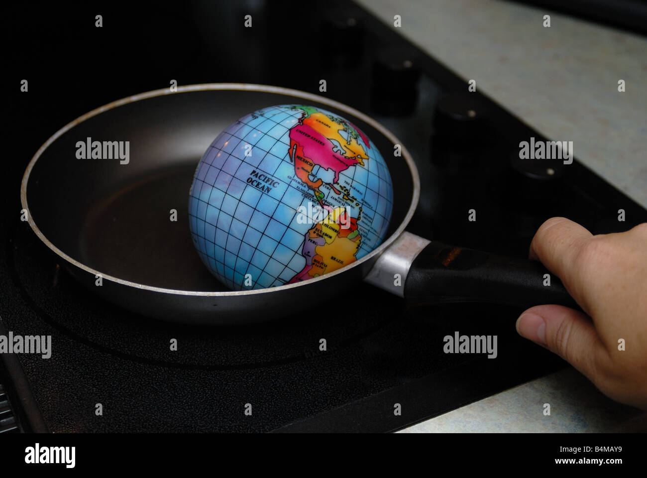 A globe is shown being fried in a skillet on a stove burner representing the concept of Global Warming - Stock Image