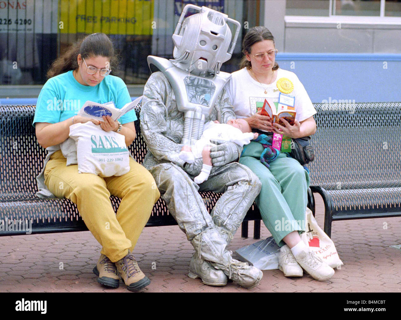 Person in robot outfit sits down on bench next to two women shoppers reading their books before a Sci Fi convention - Stock Image