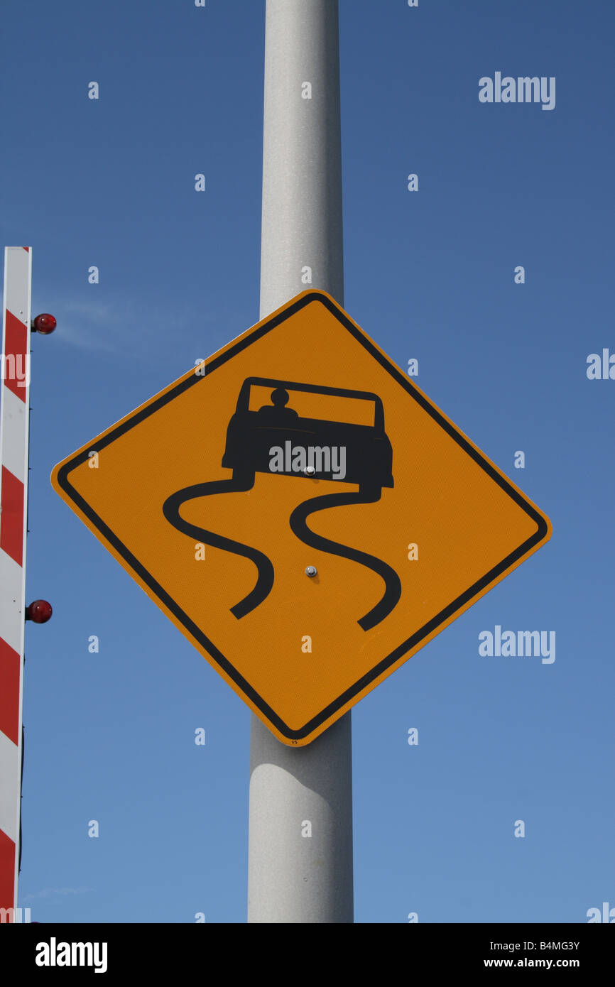 Close-up of Slippery When Wet Warning sign on bridge. - Stock Image