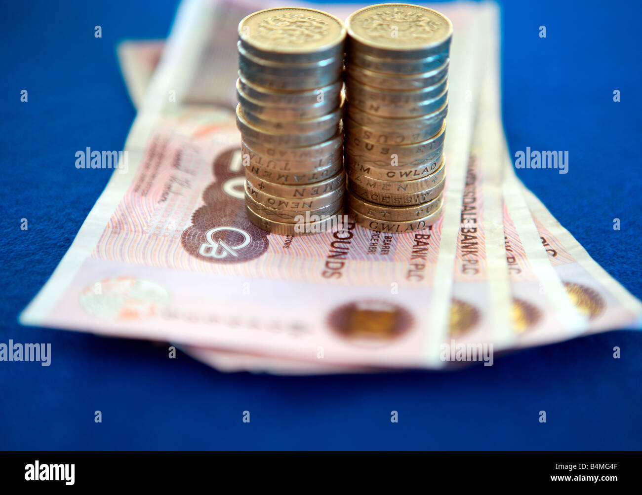 Pound coins on £20 pound notes - Stock Image