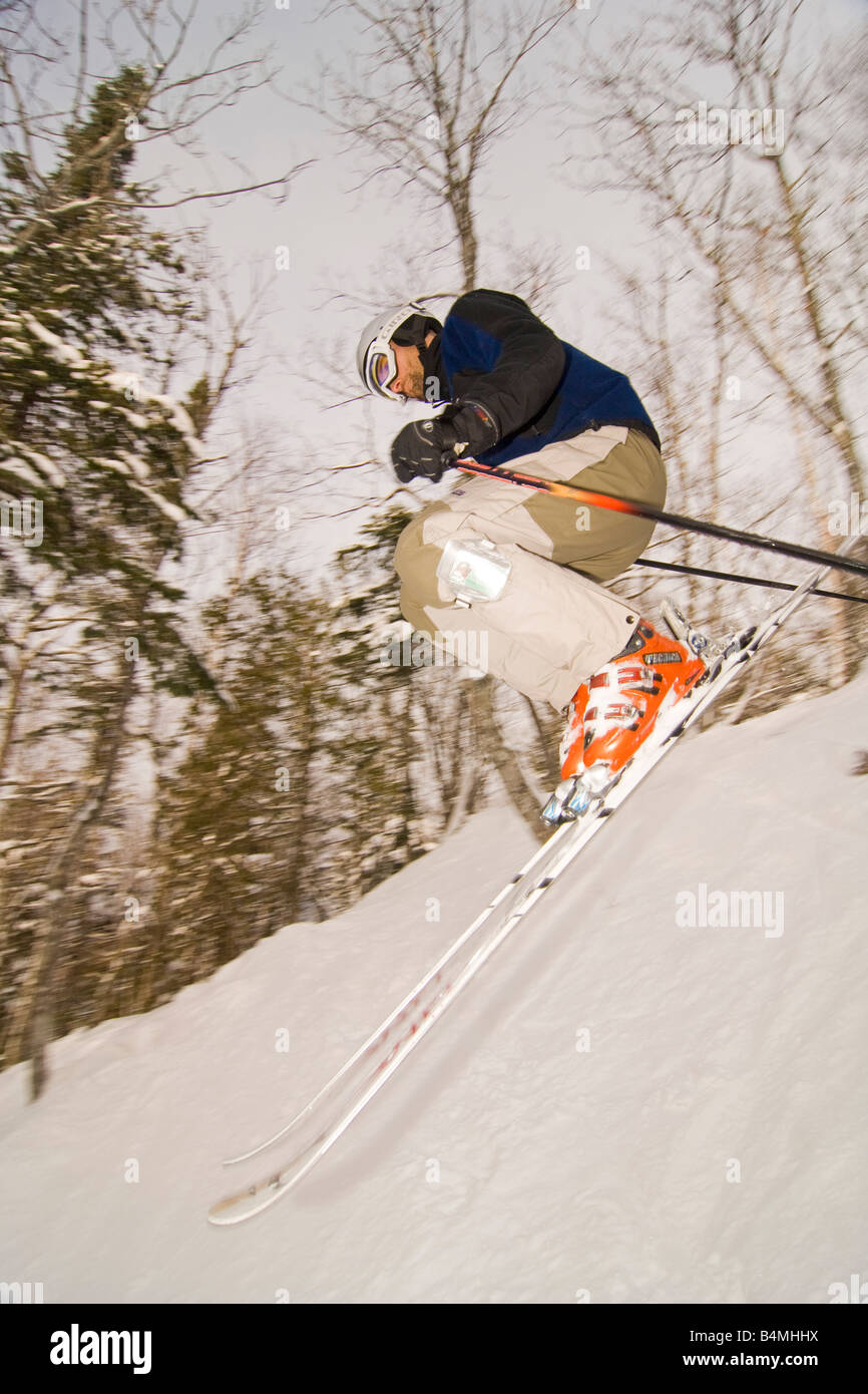 A skier goes over a jump in the extreme backcountry section of Mount Bohemia ski resort in Michigans Upper Peninsula - Stock Image