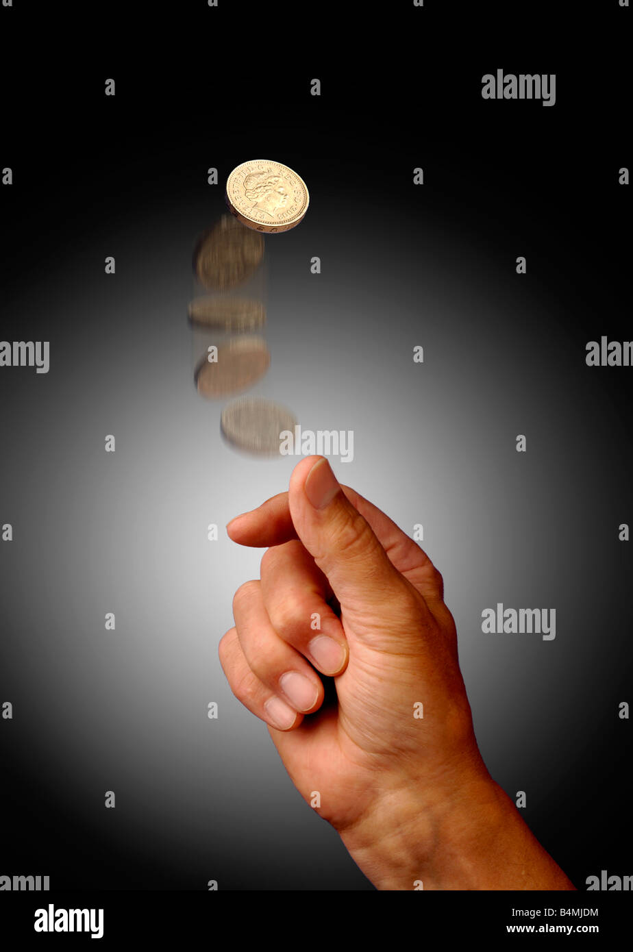 Person tossing one pound coin, studio shot - Stock Image