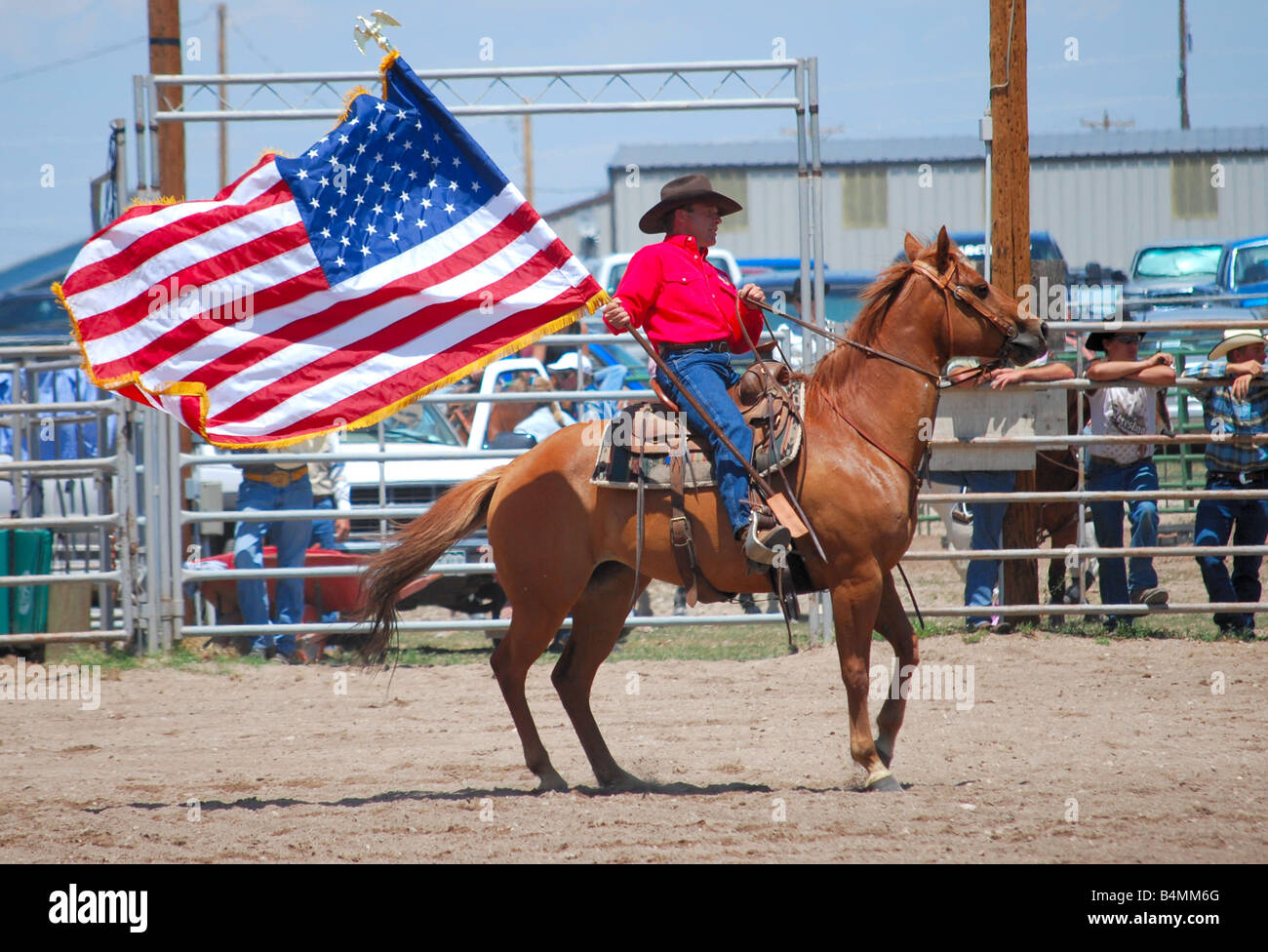 Cowboy carrying an American flag while riding on a horse at a rodeo - Stock Image