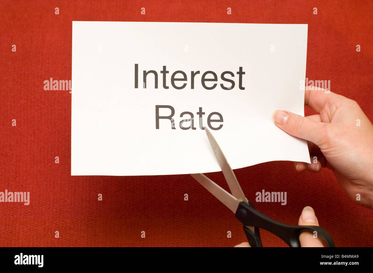 Picture of person cutting a piece of paper with 'Interest Rate' written on it using a pair of scissors - Stock Image
