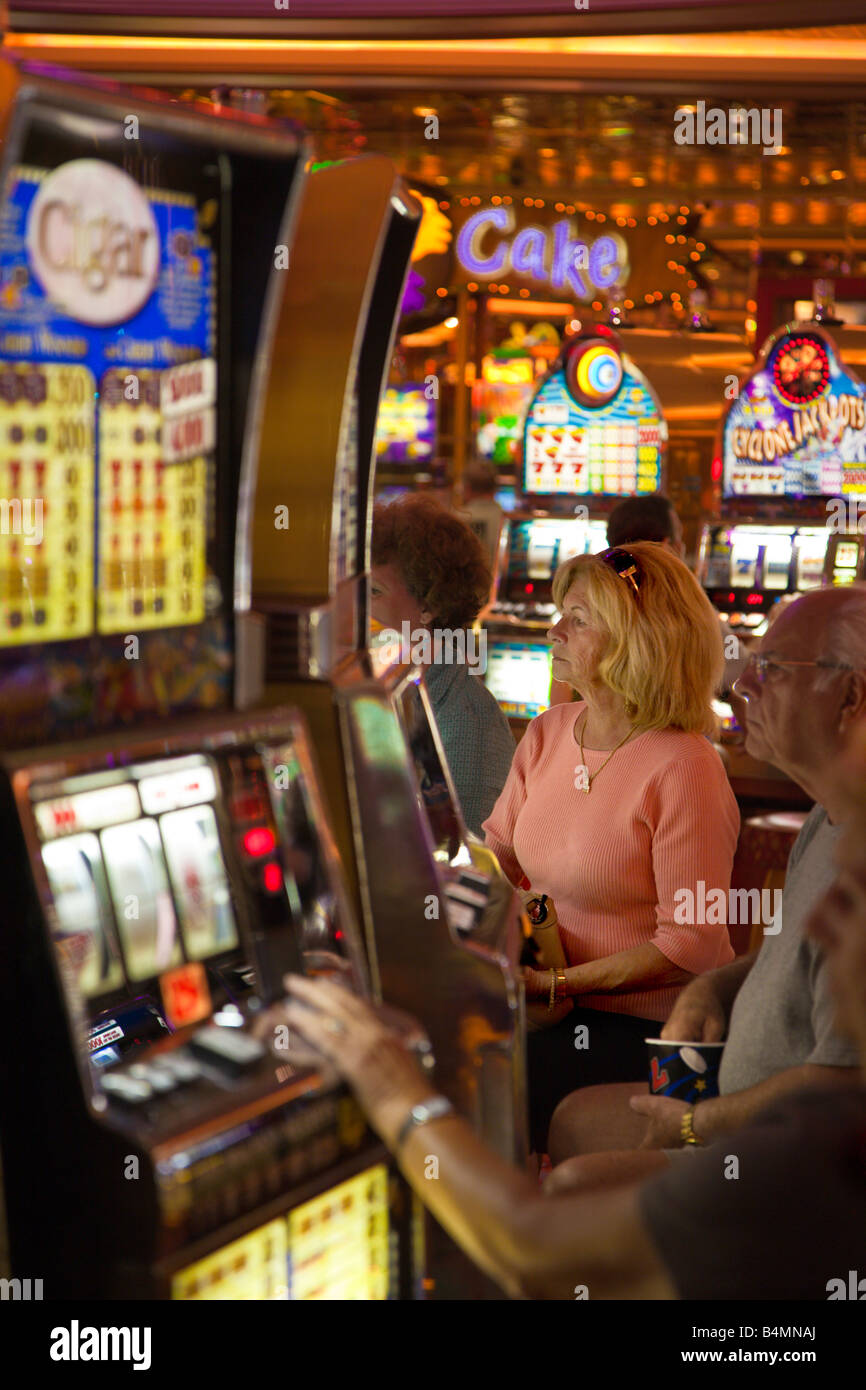 Woman playing slot machines in casino on Royal Caribbean Navigator of the Seas cruise ship - Stock Image