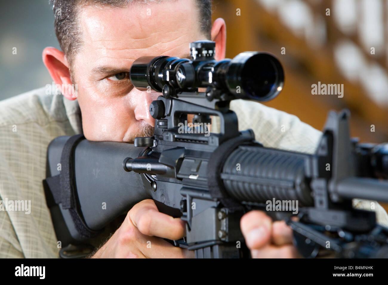 A man aims an AR 15 Bushmaster rifle Stock Photo: 20124991