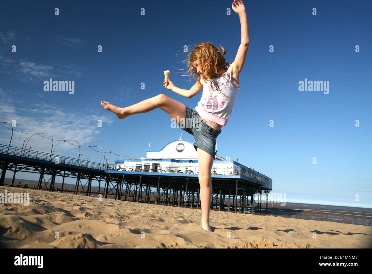 Girl  playing ice cream on the beach at Cleethorpes near Grimsby Humberside north east Lincolnshire holiday fun - Stock Image