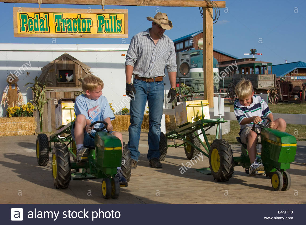 Two boys compete in a childrens version of tractor pulls as a man supervises at the Spokane Interstate Fair. - Stock Image