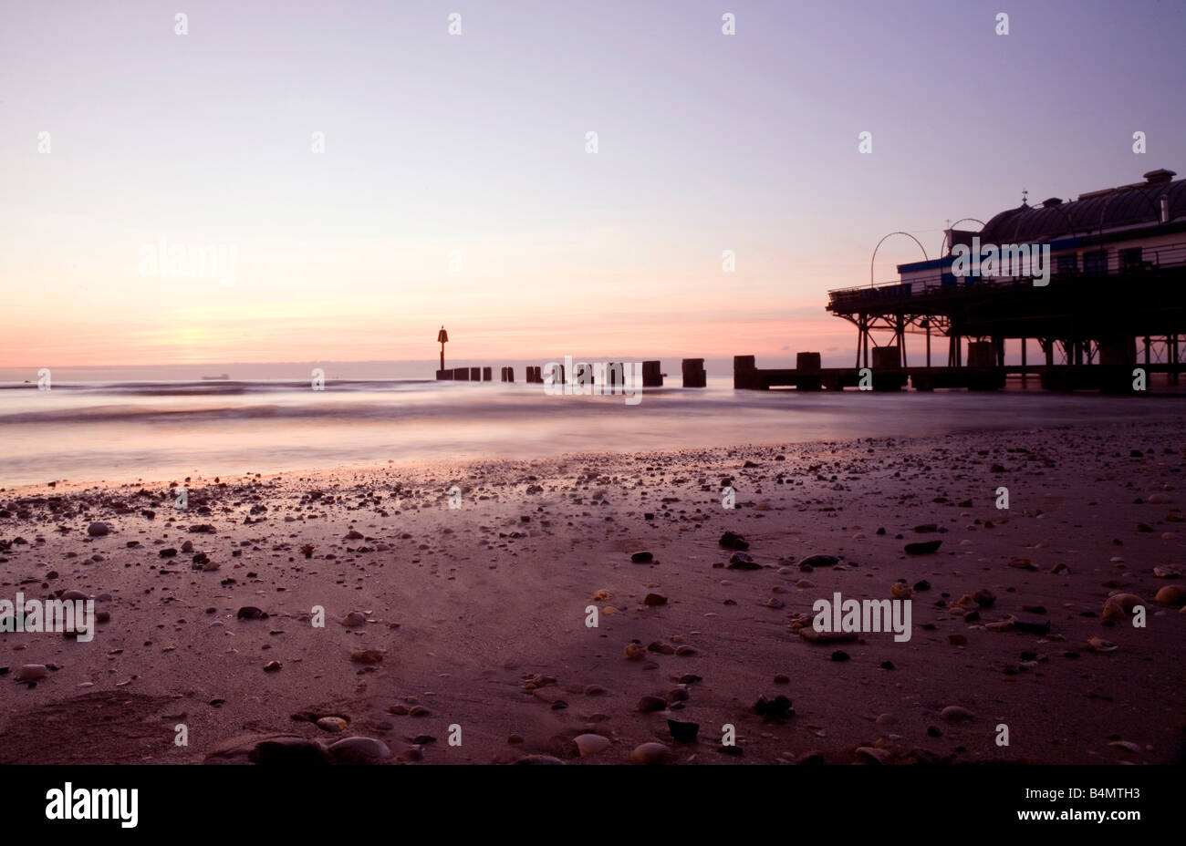 Sunrise on Cleethorpes beach with pier and beach in view in humberside near Grimsby south north east Lincolnshire - Stock Image