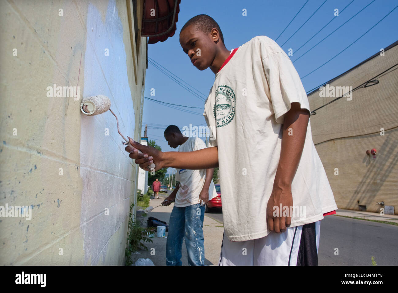 Two teenagers paint over graffiti on a blighted business in Hamden Connecticut USA for their summer job Stock Photo