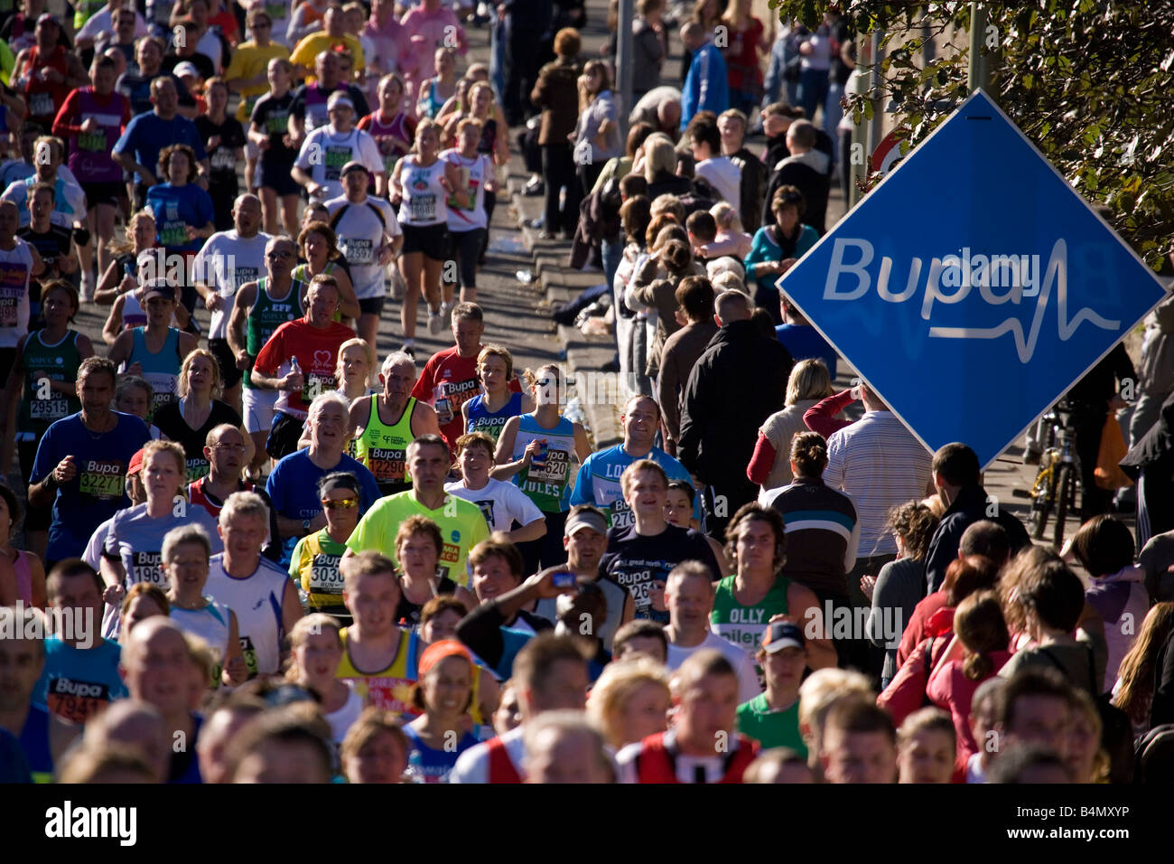 Runners go past a sign for BUPA a sponsor of the Great North Run of 2008. - Stock Image