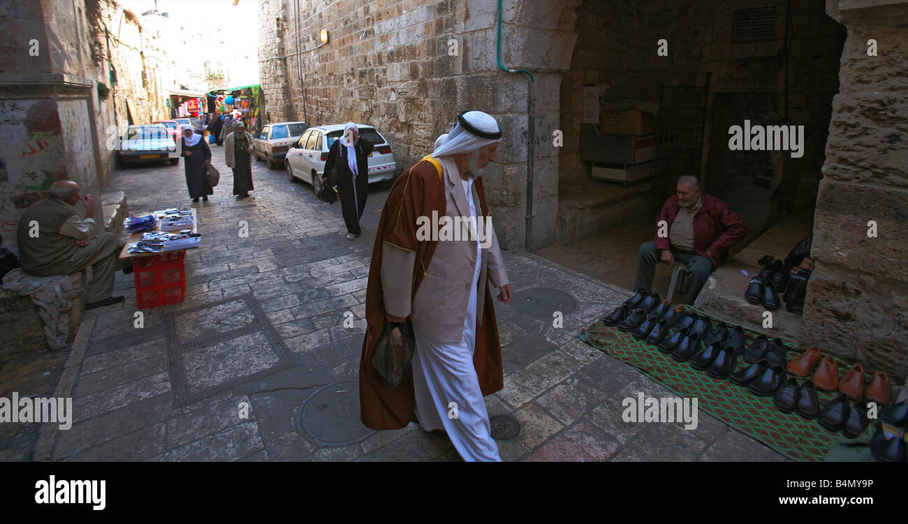 A Muslim man examines shoes at a market in the old city section of Jerusalem - Stock Image