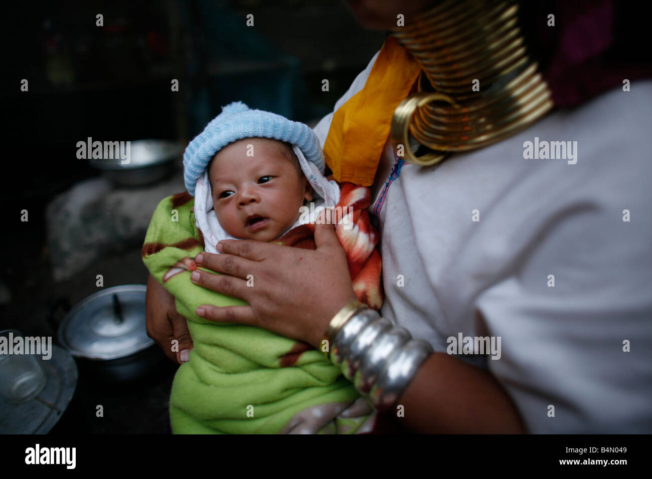 Closeup of a Longneck baby being held by its mother Approximately 300 Burmese refugees in Thailand are members of - Stock Image