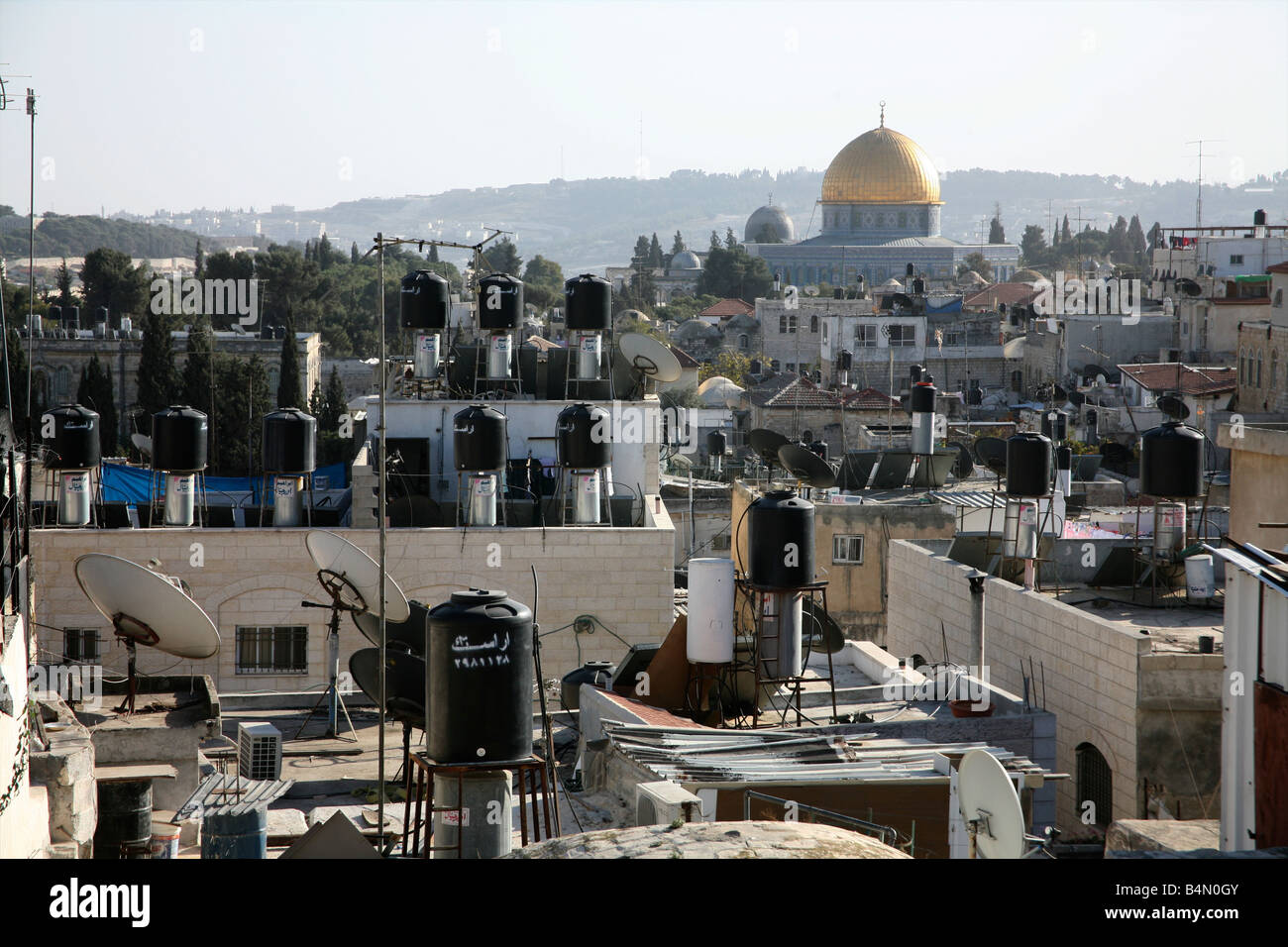 Rooftops full of chimneys and communications equipment in the old city section of Jerusalem Nearby the dome of the - Stock Image