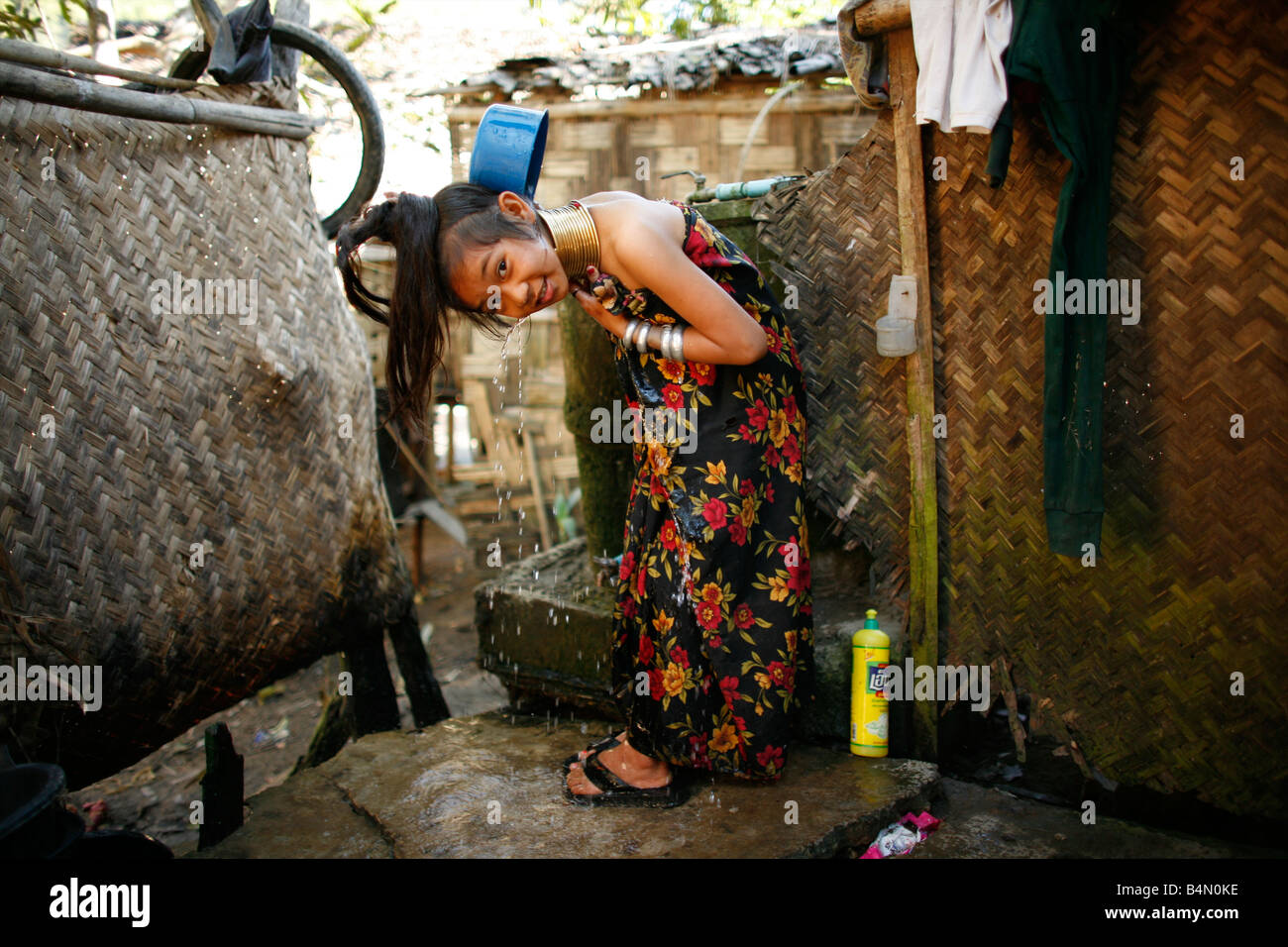 A Longneck girl showers outside her home Approximately 300 Burmese refugees in Thailand are members of the indigenous Stock Photo