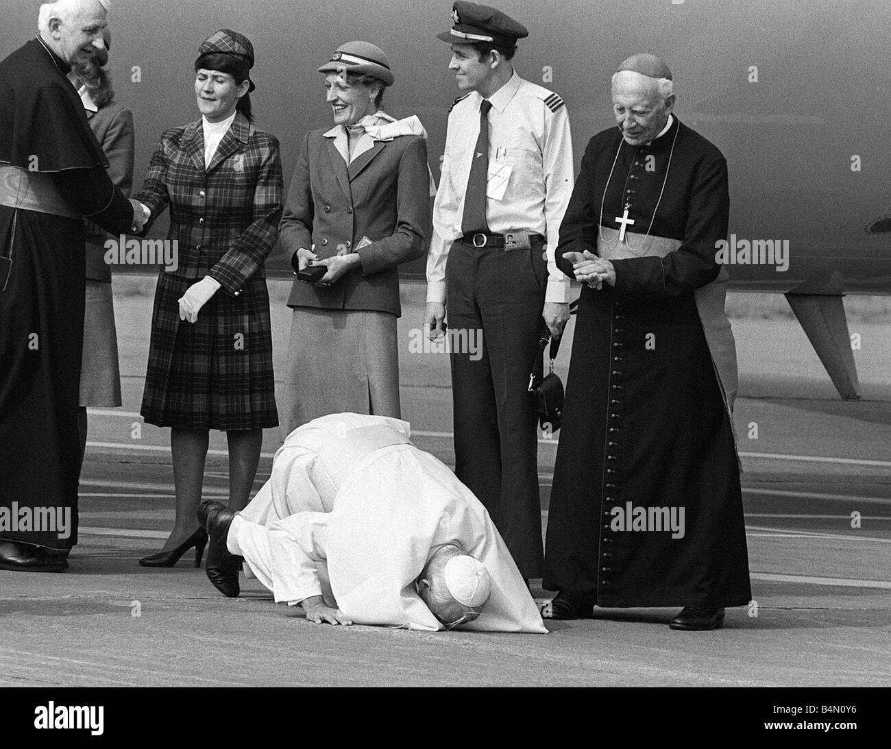Pope John Paul II kneels down and kisses the ground at Cardiff airport on his visit to Wales L Stock Photo