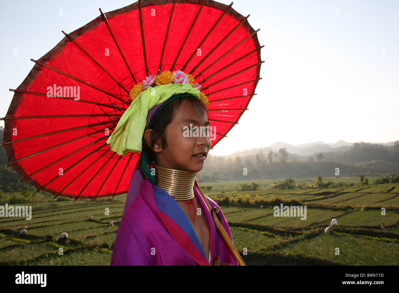 Closeup of girl walking with a parasol through the rice fields outside the Longneck village Approximately 300 Burmese - Stock Image