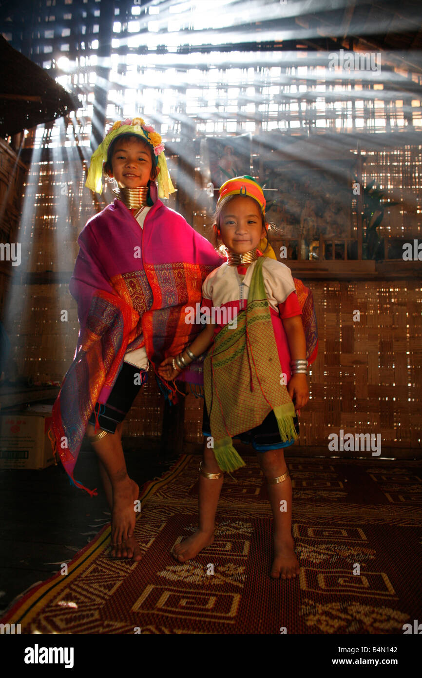 Two young Longneck girls wearing traditional dress indoors Approximately 300 Burmese refugees in Thailand are members - Stock Image