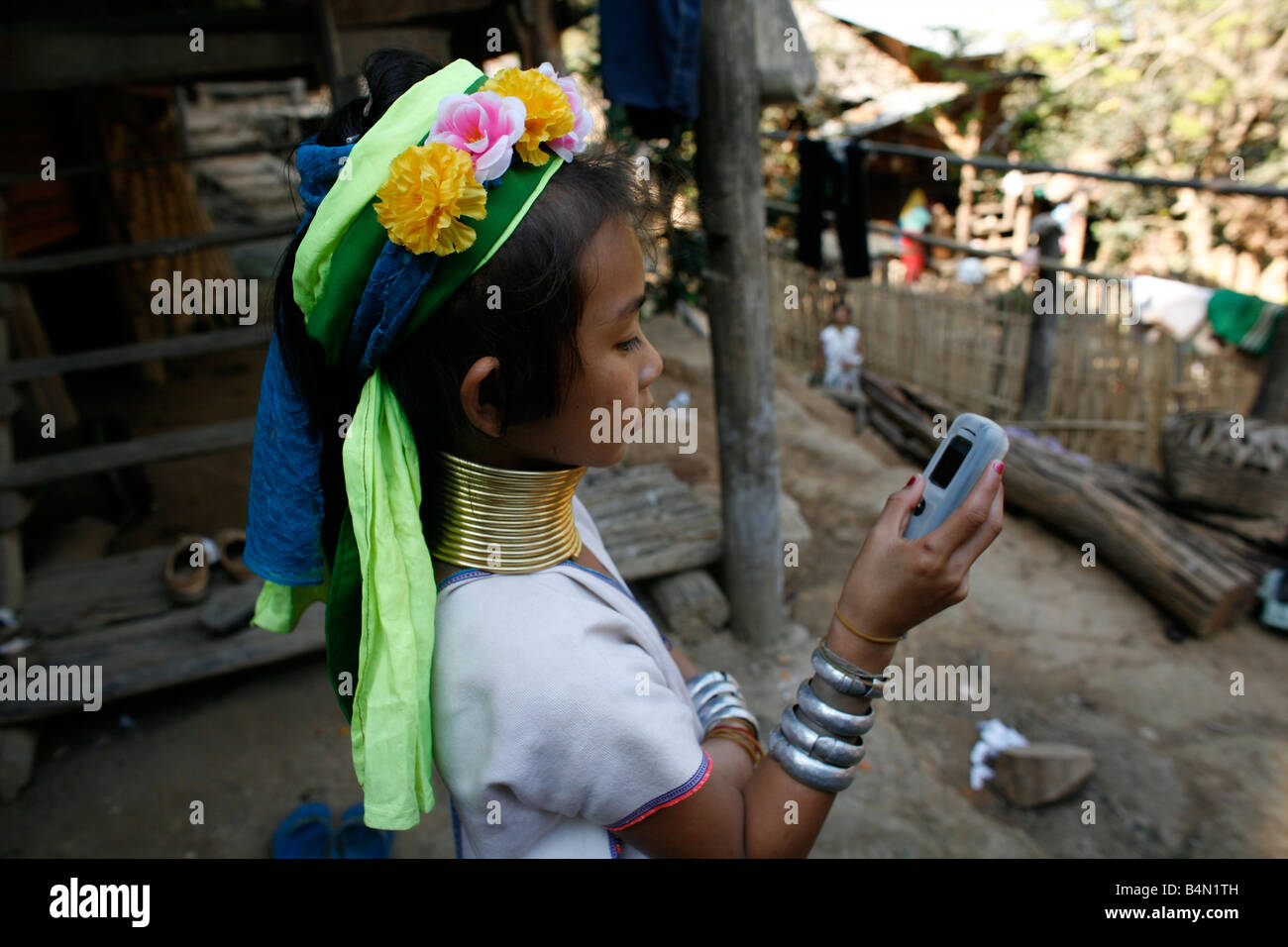 A Longneck girl examines a cell phone Approximately 300 Burmese refugees in Thailand are members of the indigenous - Stock Image