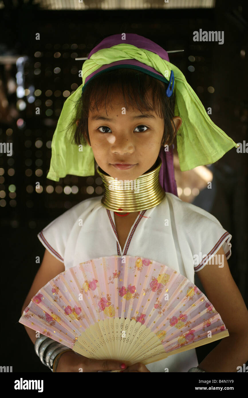 Portrait of a young Longneck girl with a fan Approximately 300 Burmese refugees in Thailand are members of the indigenous - Stock Image