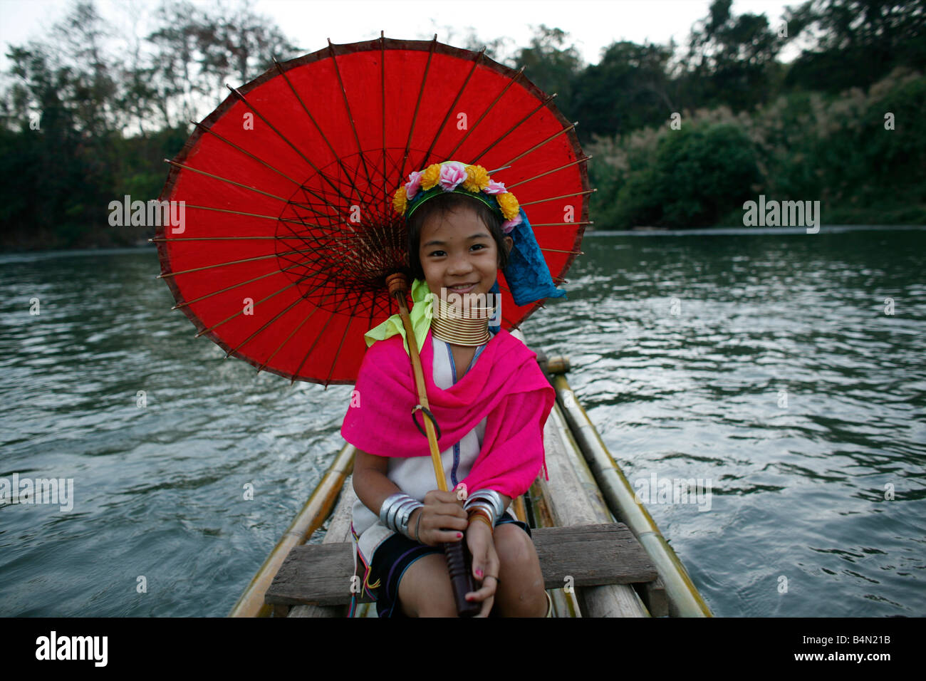 Longneck girl holds a parasol on a boat Approximately 300 Burmese refugees in Thailand are members of the indigenous Stock Photo