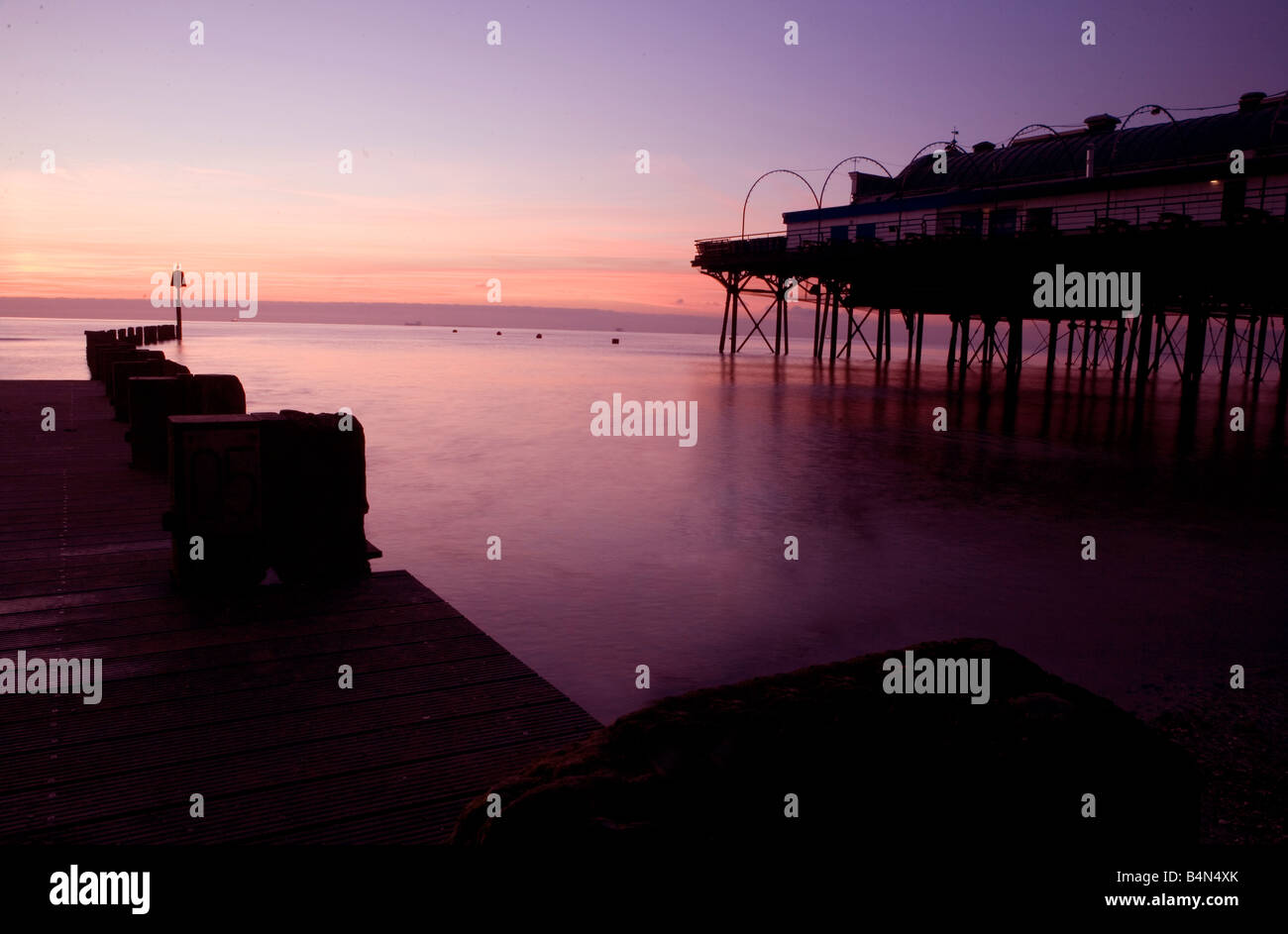 Sunrise on cleethorpes beach with pier and jetty near Grimsby south Humberside north east Lincolnshire flat sea - Stock Image