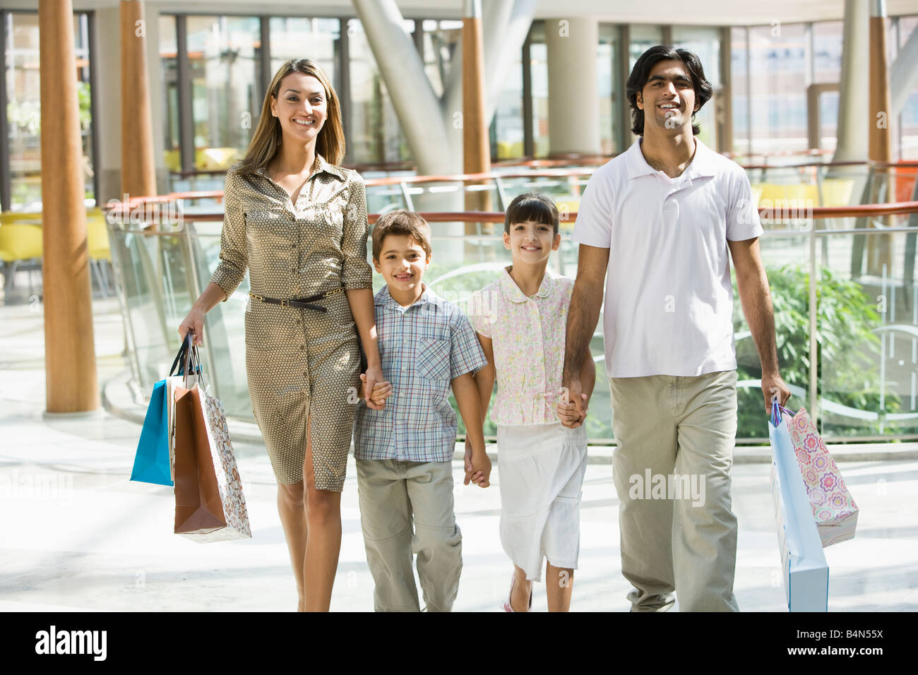 Family walking in mall holding hands and smiling (selective focus) - Stock Image