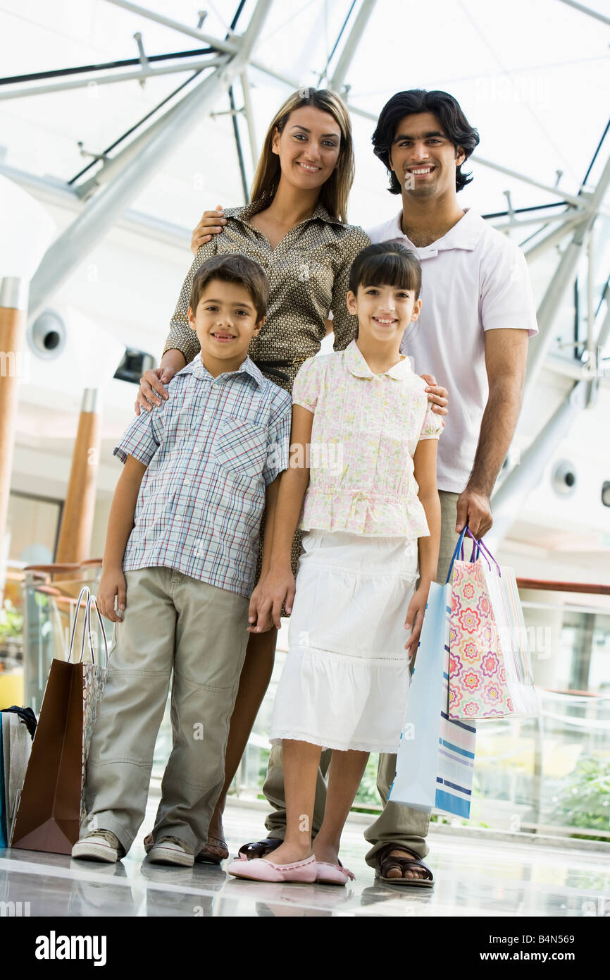 Family standing in mall smiling (selective focus) - Stock Image