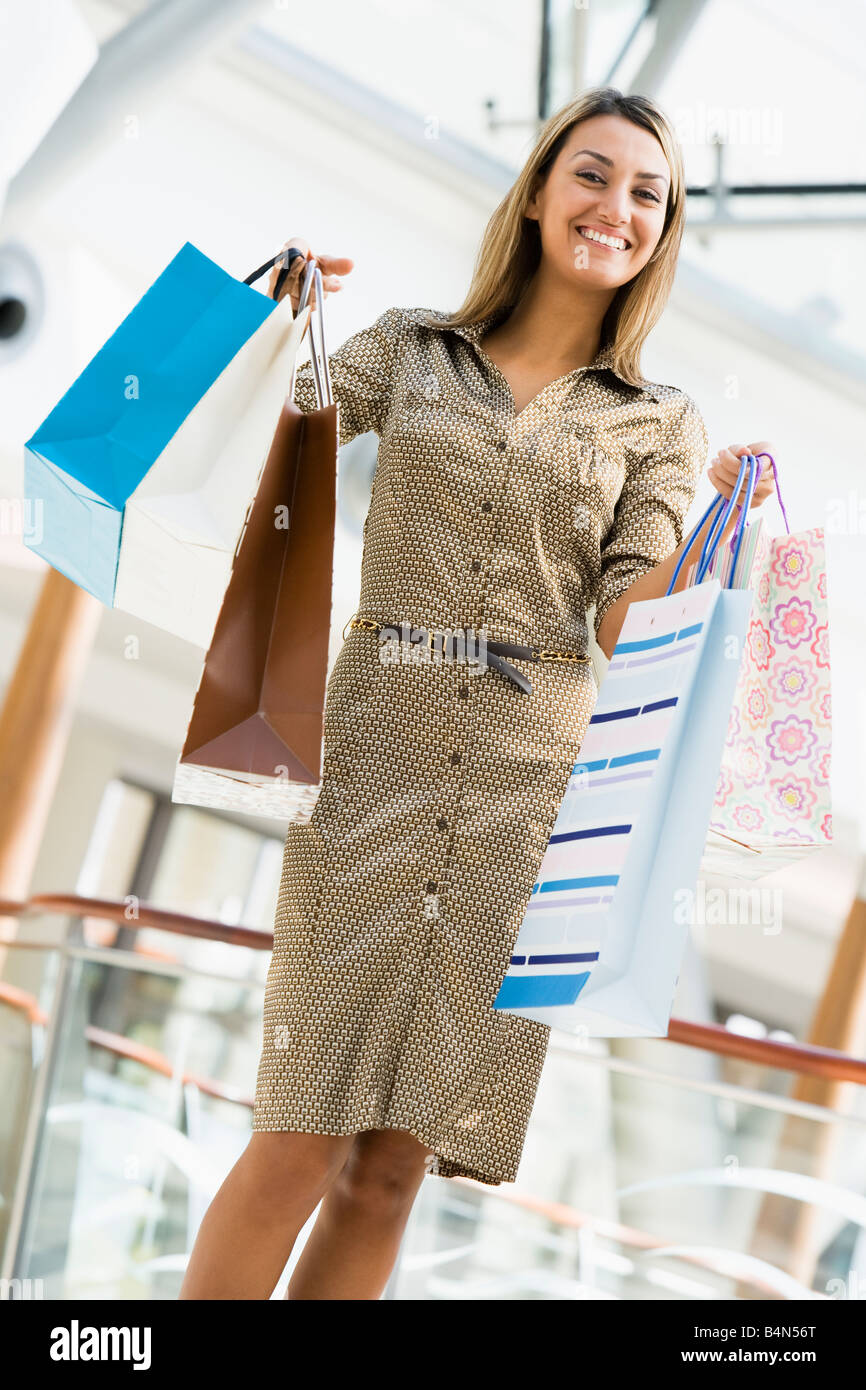 Woman standing in mall smiling (selective focus) - Stock Image