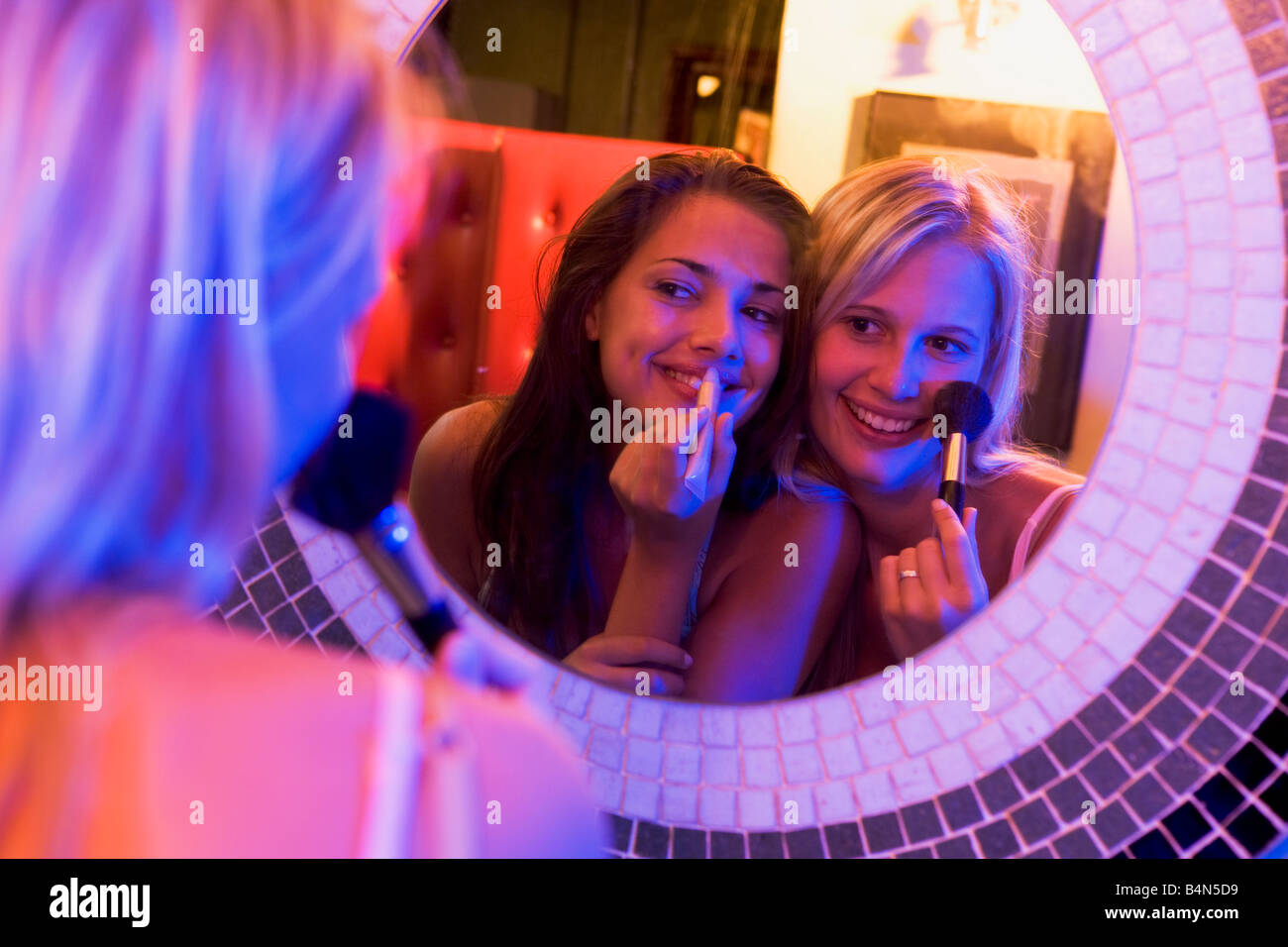 Two young women applying makeup in a mirror Stock Photo