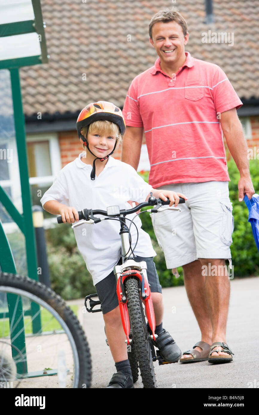 Father and Son outside school with bicycle - Stock Image