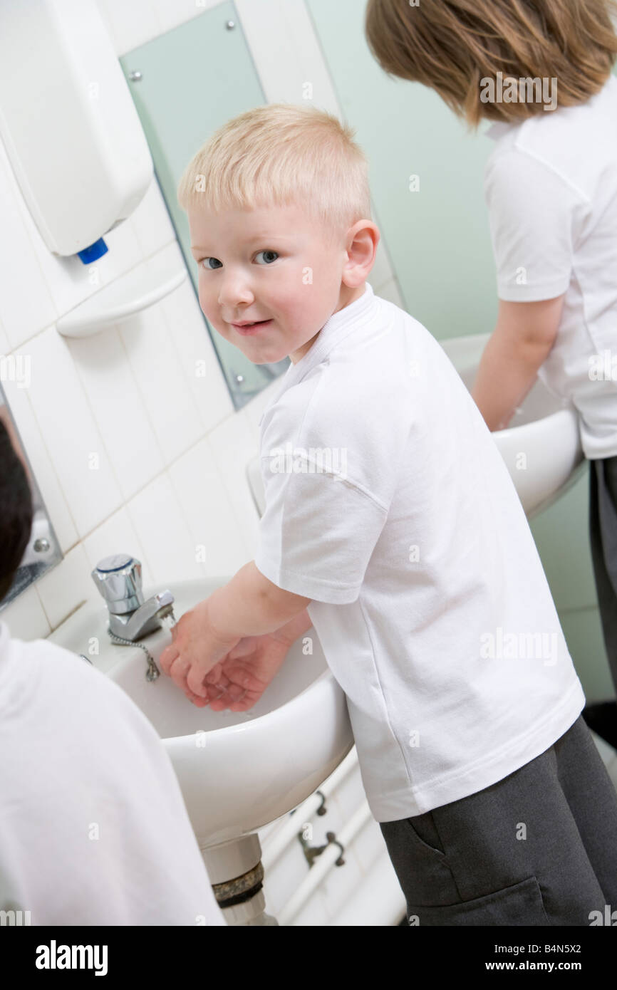 Students in bathroom at sinks washing hands - Stock Image