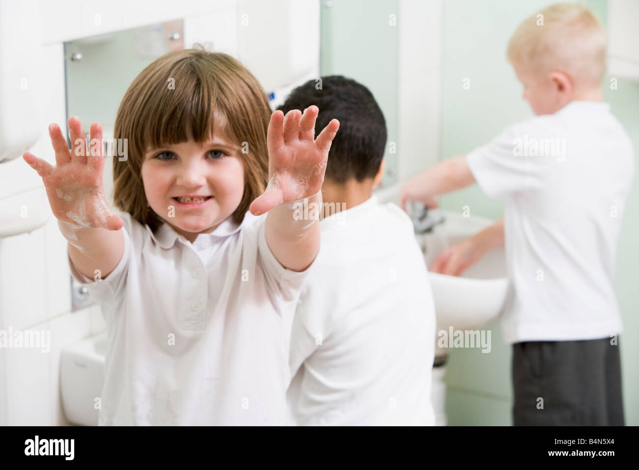 Students in bathroom at sinks washing hands with one holding up soapy hands (selective focus) - Stock Image