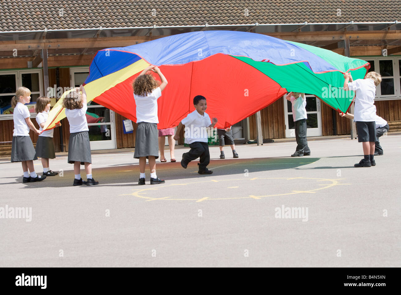 Students outdoors during recess playing with a parachute - Stock Image