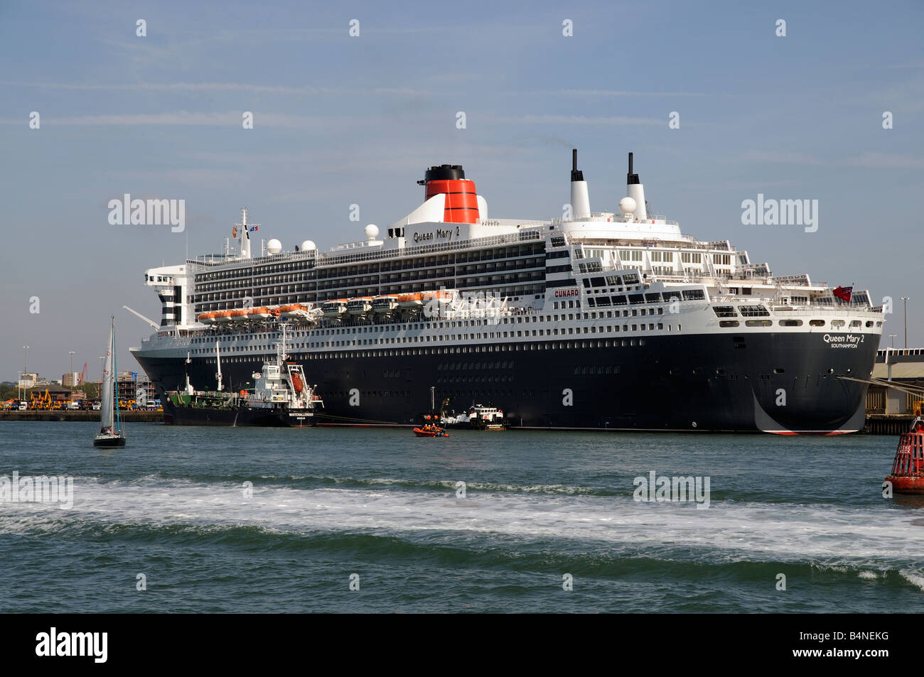 Port of Southampton England UK Queen Mary 2 and MV Whitchallenger a fuel oil bunkering vessel alongside - Stock Image