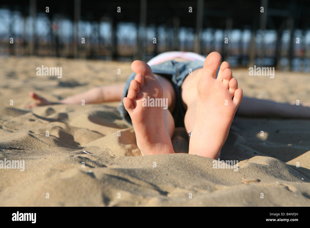 Girl sun bathing on the beach at Cleethorpes near Grimsby south Humberside north east Lincolnshire holiday fun on - Stock Image