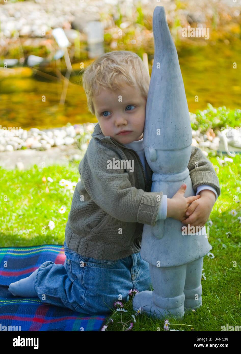 Little boy with modern garden gnome Stock Photo - Alamy