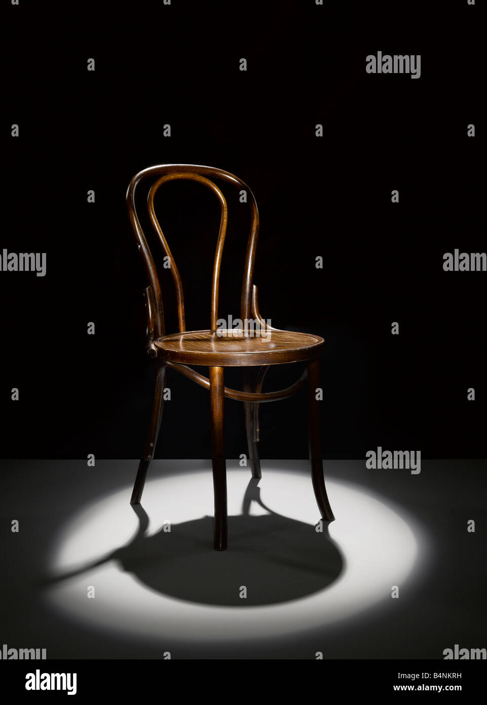 A wooden chair in the spotlight - Stock Image